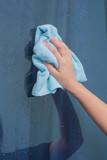 women hand using blue rag wipe the glass