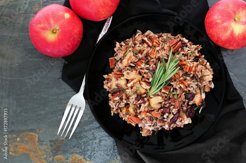 Autumn rice pilaf with apples, nuts and cranberries, overhead scene against a slate background