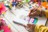 The girl draws a cake with bright colored markers. Gifts, rosettes, confetti and festive accessories. - 172902740