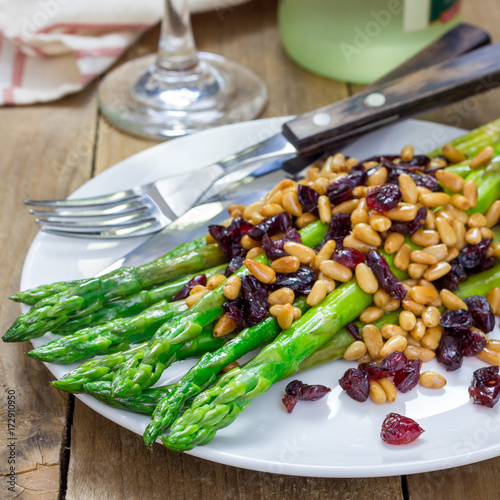 Freshly cooked asparagus appetizer with pine nuts and cranberries on white plate Poster
