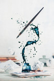 Spilled ink flying above inkwell in a spiraling splash with tiny drops and flying pen on a light background. Still life with writer workplace. Creative writing concept. - 172920516