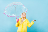 Woman wearing raincoat holding umbrella checking weather - 172922381