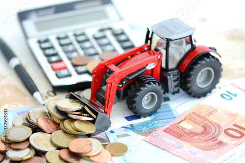 Aluminium Trekker Analyzing financial result in agriculture with tractor pushing a lot of money near office tools
