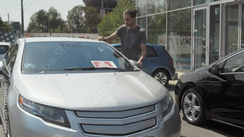 Foto op Canvas Stadion Young man choose the automobile in the car showroom outdoors