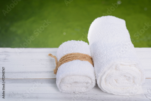 Fotobehang Spa Spa wellness concept,white towels on white wood table with green pond background