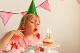 happy little girl make wish blow candles at birthday party - 172986309