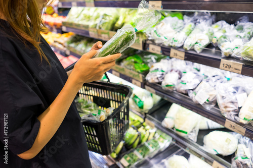 Young asian woman with shopping basket choosing products in supermarket