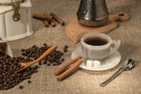 freshly ground hot coffee with grains and cinnamon on the table - 172992716