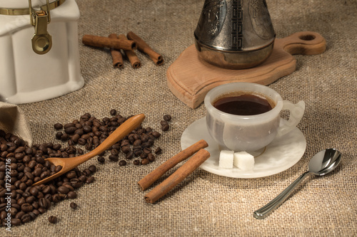 Fotobehang Koffiebonen freshly ground hot coffee with grains and cinnamon on the table