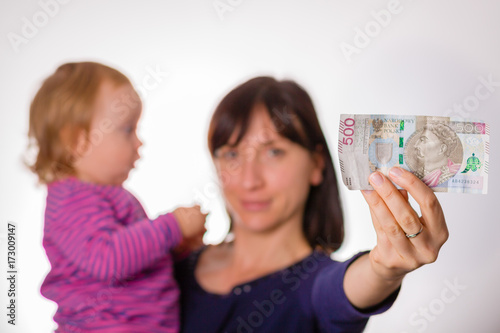 Poster Mother with little daughter holds in hand 500 zloty banknote