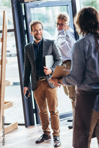 waiter greeting businessmen in cafe Poster