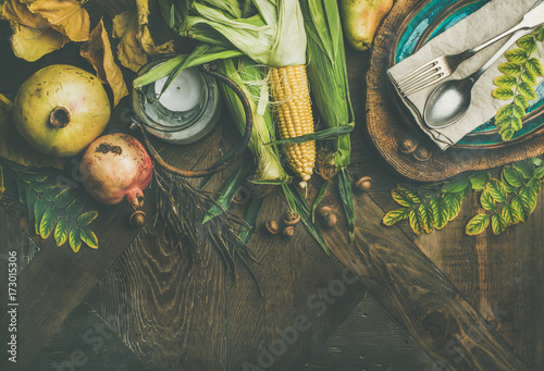 Fall table setting for Thanksgiving day. Flat-lay of plate, cutlery, candle, Autumn harvest vegetables, fruit and fallen yellow leaves for decor over rustic wooden background, top view, copy space - 173015306