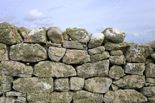 Foto op Plexiglas Baksteen muur Natursteinmauer vor bewölktem Himmel
