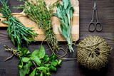 bundle of sage and thyme on wooden board top view - 173020325