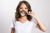 Young girl holding magnifier over her teeth  - 173042312