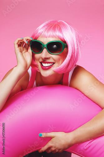 jolie femme perruque cheveux roses souriant avec baudruche et lunettes de soleil Poster