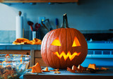 creepy halloween jack o lantern pumpkin in kitchen glowing right after it was carved - 173075129