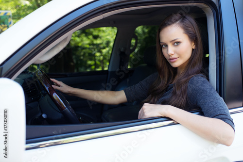 Beautiful young happy woman in car.