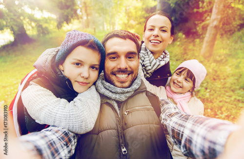 Foto Murales family with backpacks taking selfie and hiking