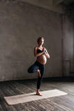 Young beautiful  pregnant yoga posing in studio - 173121707