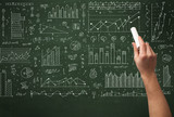 A business person drawing data on chalkboard - 173180123