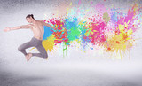 Modern street dancer jumping with colorful paint splashes