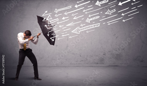 Business man standing with umbrella and drawn arrows hitting him - 173181142