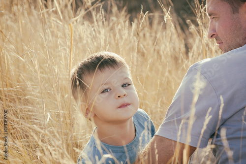 father and son are sitting in the field, father hugs his son, toned photo © Irina