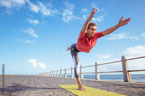 Fotobehang School de yoga Woman doing virabhadrasana yoga pose at the seaside