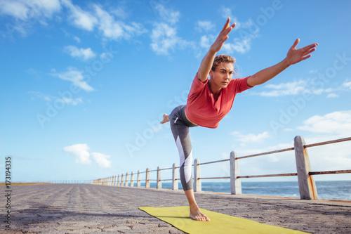 Fototapeta Woman doing virabhadrasana yoga pose at the seaside