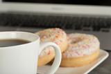 Zwei Donuts, Tasse Kaffee und ein Laptop im Hintergrund