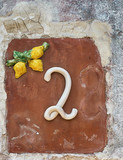 Old stone wall with the number 2 in ceramic. - 173227782