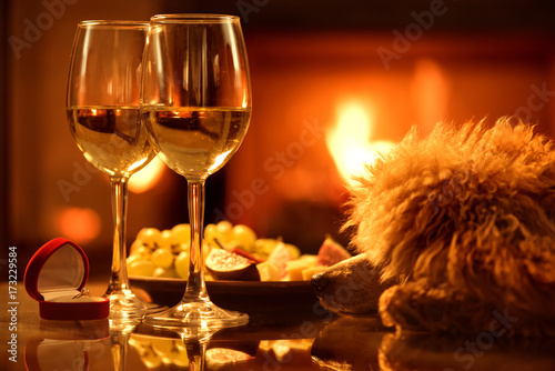Two  wine wineglasses with the red box with engagement ring over fireplace background Poster