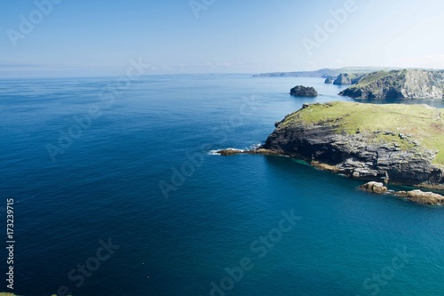 An aerial view from clifftops looking out to the horizon of a deep, blue, calm ocean at Tintagel in Cornwall, UK which is the seat of the legendary English King Arthur and shows cliffs Poster
