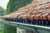 Drops of water flow into the eaves on the house in the rain. - 173257972