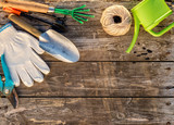 Gardening tools and watering can on wooden background - 173271199