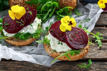 Rustic wholegrain buns with cottage cheese, rocket leaves, beetroot slices and edible viola flowers. Vegetarian food snack.