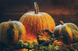 solid crust of pumpkin. on a wooden background. toned. grass and branches. halloween style