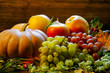 bright pumpkins, grapes and apples on branches and grass on a wooden background. halloween