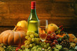 a bottle and a glass of grape wine and bright pumpkins, grapes and apples on branches and grass on a wooden background. holiday halloween