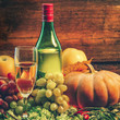 grape wine and bright pumpkins, grapes and apples on a wooden background. holiday halloween