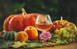 pumpkins and grapes, a peach and an apple. a glass of wine. on a blurred background