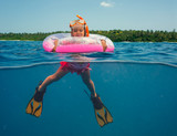 Little girl with a float, mask and fins in the ocean - 173299930