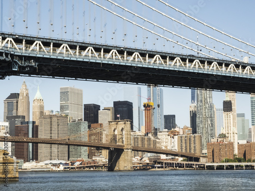 Foto op Plexiglas Brooklyn Bridge Manhattan Bridge and Brooklyn Bridge with Manhattan skyline background from Brooklyn early in the morning with blue sky and sun shine - Brooklyn, New York, NY, United States of America, USA