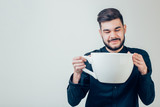 business man holding a funny huge and oversized cup of black coffee in caffeine - 173304309