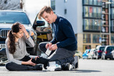 Young male driver using a sterile adhesive bandage from his first aid kit to help an injured female bicyclist on the street - 173309720