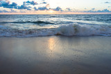 gentle waves crashing on the shore and reflecting sunlight - 173310161