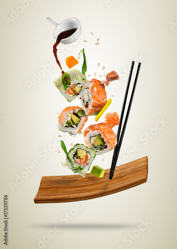 Foto op Canvas Sushi bar Flying sushi pieces served on wooden plate, separated on soft background