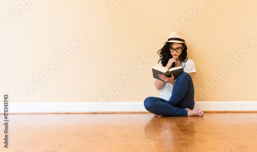 Young woman reading a book in a big room