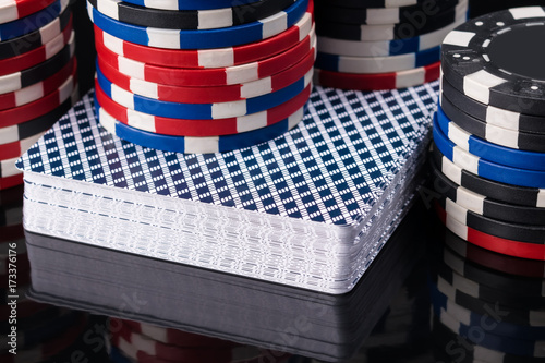 deck of poker cards on a black background with poker chips Poster